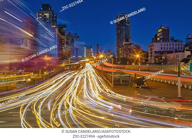 Hectic Manhattan NYC - View to the Ed Koch Queensboro Bridge on 59th Street in midtown Manhattan in New York City, NY. The long exposure creates streaks of...
