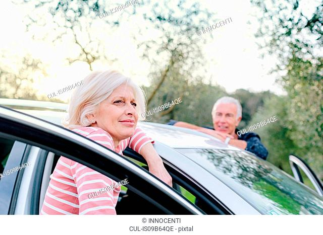 Tourist couple looking out from car doors in rural spot, Siena, Tuscany, Italy