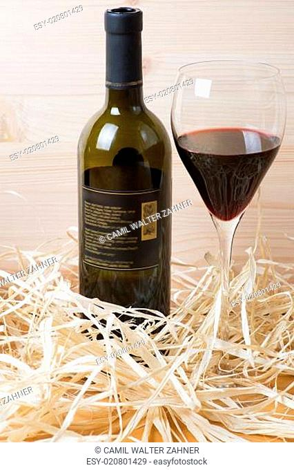 Bottle and glass of red wine in straw
