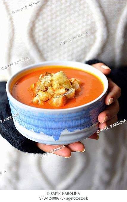 A woman holds a plate of pumpkin soup with croutons