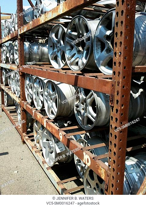 Used automotive wheels for resale on a large rack at a junkyard in Spokane, Washington, USA