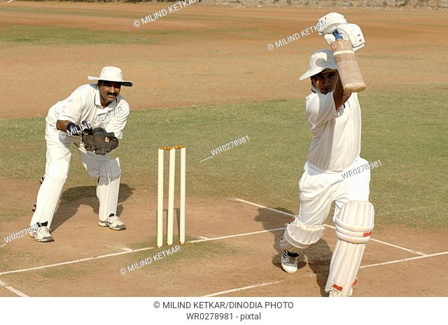 Indian right handed batsman in action playing cover drive shot in cricket match MR705L
