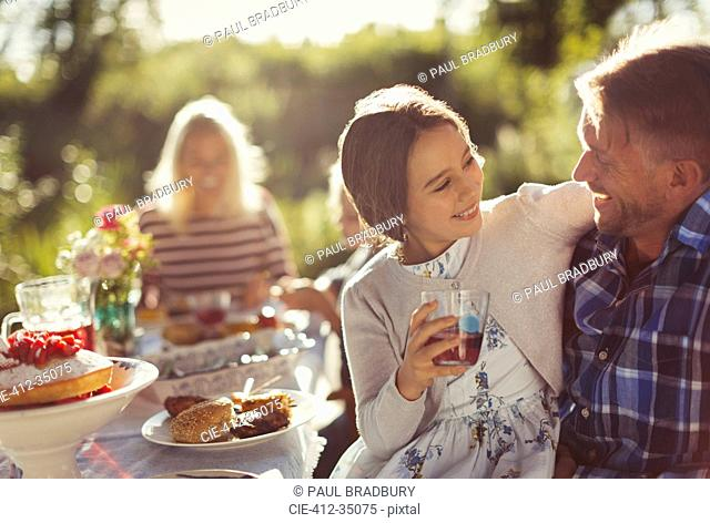 Affectionate father and daughter enjoying sunny garden party