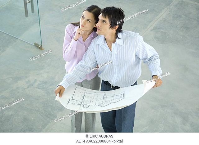 Young couple holding blueprints, looking up, high angle view