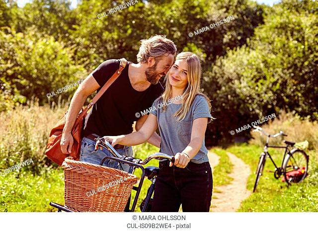 Portrait of couple with bicycles laughing on rural dirt track