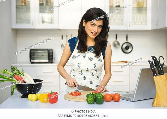 Woman chopping tomatoes in the kitchen