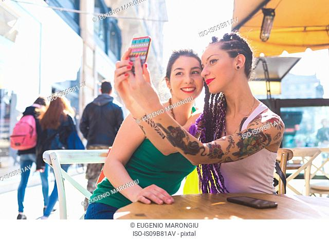 Women on city break at outdoor cafe taking selfie, Milan, Italy