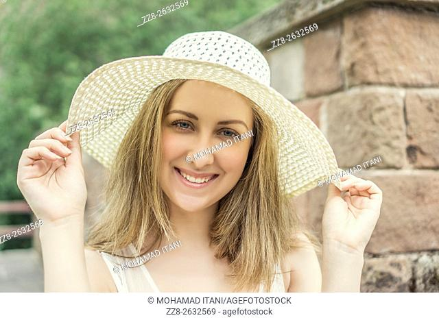 Happy beautiful woman holding her hat outdoors