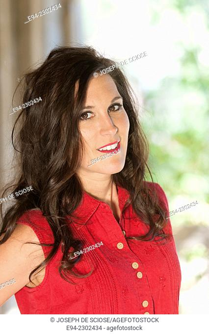 A portrait of a smiling 36 year old brunette woman looking directly at the camera, outdoors
