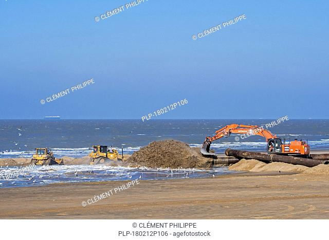 Bulldozers and hydraulic excavator installing pipeline during sand replenishment / beach nourishment works along the Belgian coast at Ostend, Belgium