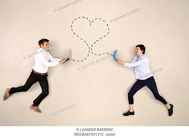 Two business colleagues connected via laptop and heart-shaped dotted line