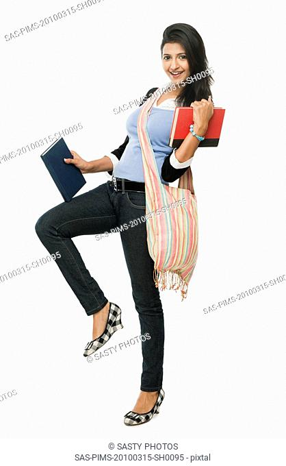 University student holding books and smiling