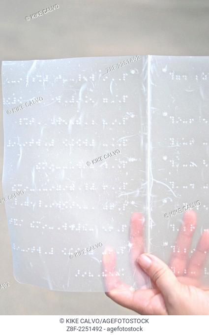 Blind woman holding a page written in braille