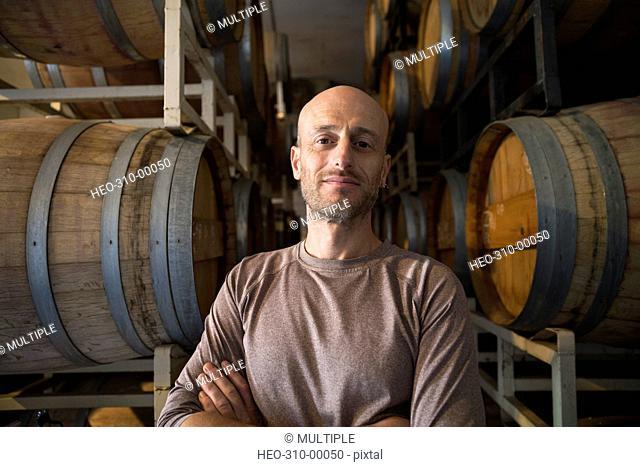 Portrait confident vintner in winery barrel room