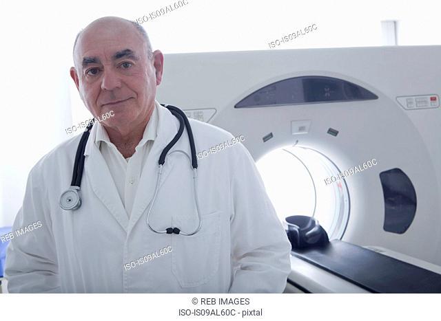 Doctor standing beside CT scanner