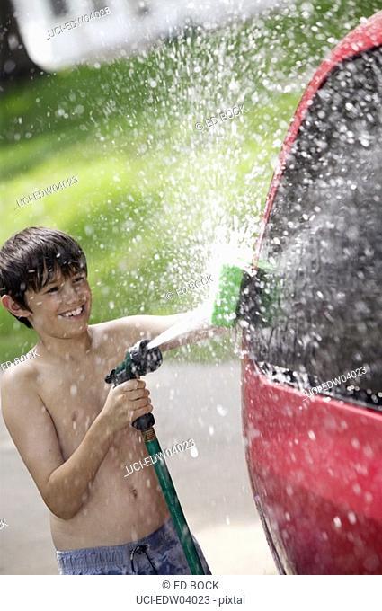 Young boy washing the car