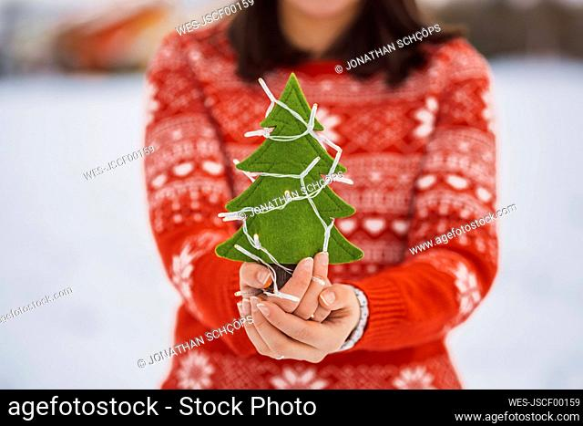 Close-up of woman holding Christmas tree with lights while standing outdoors during winter