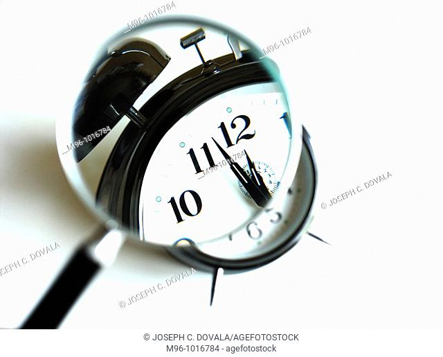 Magnifying glass over clock about to strike twelve'o'clock