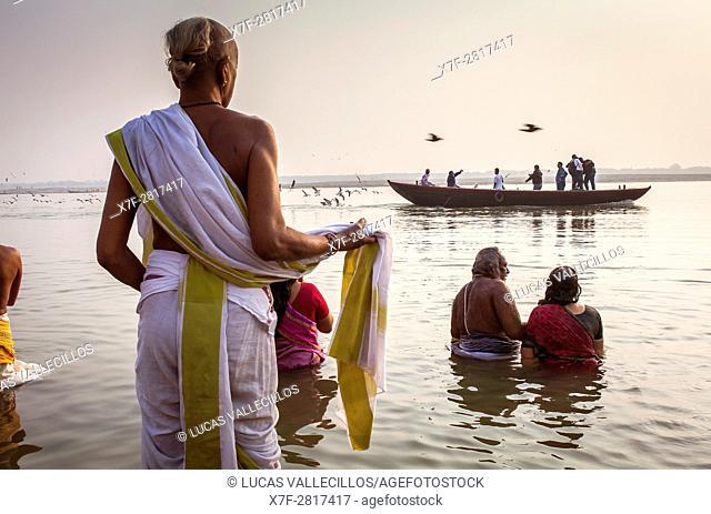 Pilgrims praying and bathing, in the ghats of Ganges river, Varanasi, Uttar Pradesh, India