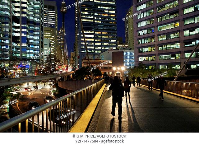 pedestrians on overpass with Sydney offices at night, Australia