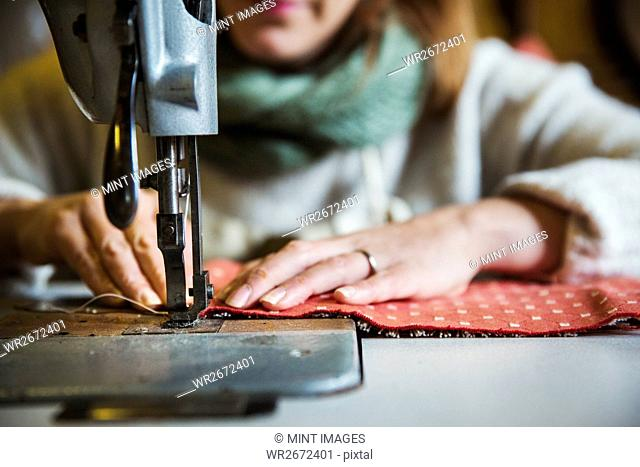 Upholstery workshop. A woman seated working with an industrial sewing machine, stitching fabric