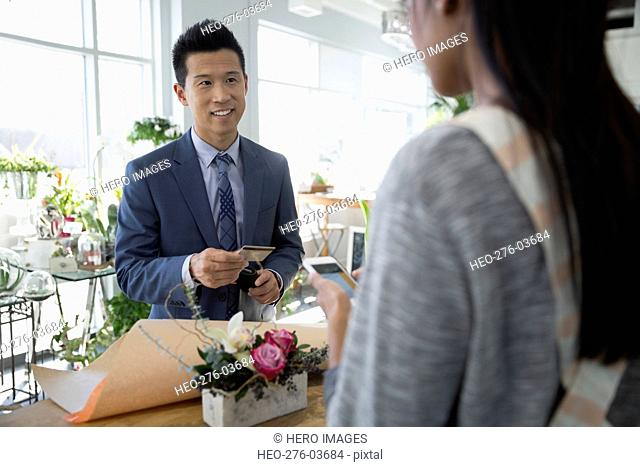 Man paying florist for bouquet in flower shop
