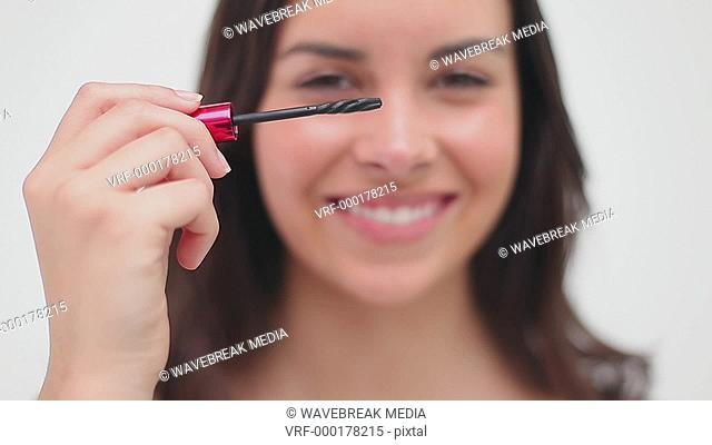 Happy brunette woman using mascara against a white background