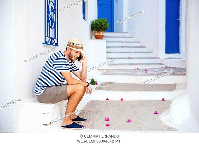 Greece, Amorgos island, young man talking on cell phone