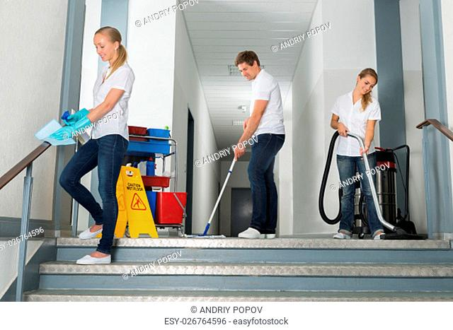 Group Of Happy Male And Female Janitor Cleaning Corridor With Cleaning Equipments