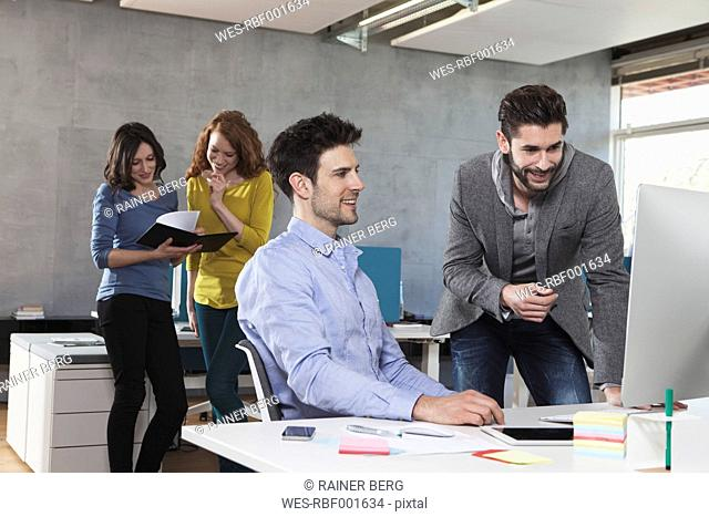 Four colleagues in an open space office