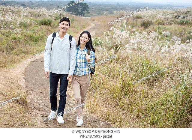 Smiling young couple with backpacks walking hand in hand on path through silver grass field