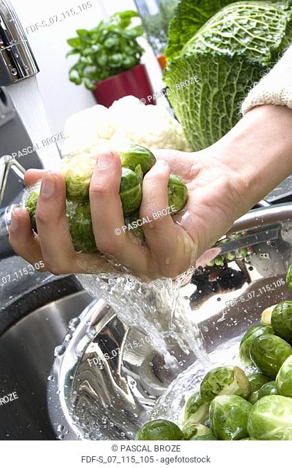 Close-up of a person's hands holding Brussels sprouts under running water in a colander
