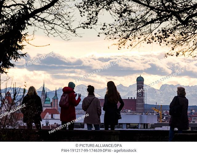 17 December 2019, Bavaria, Munich: Walkers on the Luitpoldhügel hill in the Schwabing district look over the Bavarian capital