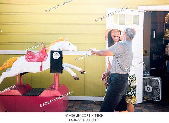 Senior couple standing beside funfair ride, laughing, Long Beach, California, USA