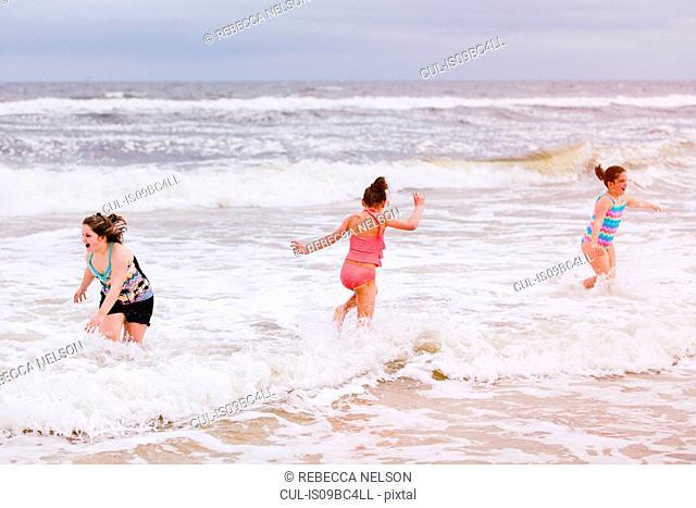 Three girls playing in ocean waves, Dauphin Island, Alabama, USA