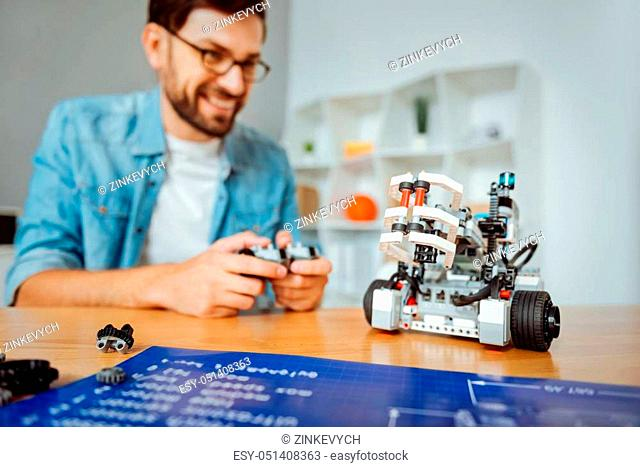 Does it work. Selective focus of robot standing on the table while professional smiling engineeer holding remote control and testing it