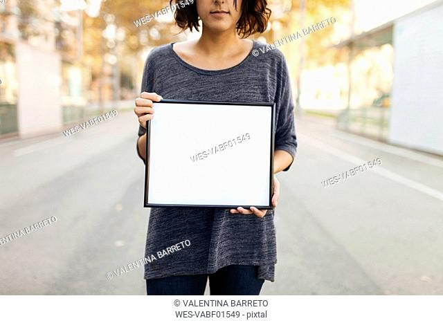 Close-up of woman holding blank frame on the street