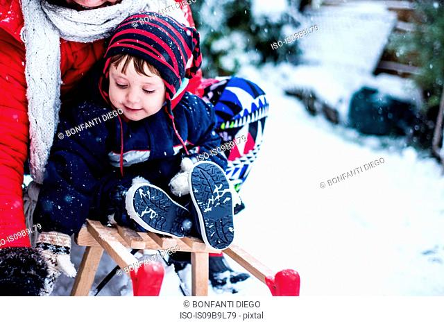 Mother and son in snow on toboggan