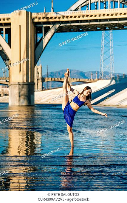 Dancer ankle deep in water, leg raised, balancing on one leg, in front of bridge, Los Angeles, California, USA