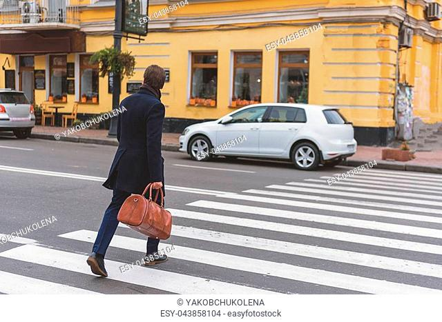 Businessman is crossing the street in a hurry. He is carrying bag. Focus on his back