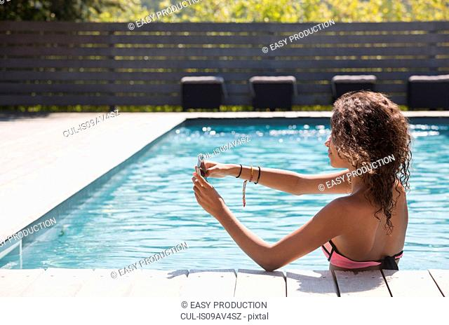 Girl in swimming pool taking smartphone selfie, Cassis, Provence, France
