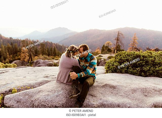 Couple sitting on rocks in mountains, Sequoia national park, California, USA