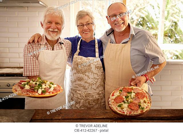 Portrait smiling, confident senior friends making pizza in cooking class