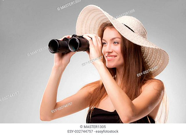 Young woman in hat looking through binoculars isolated on gray background. Travel and adventure concept. Closeup