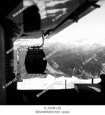 Gondola hanging from lift machinery in snowy landscape