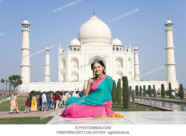 Woman sitting in front of a mausoleum, Taj Mahal, Agra, Uttar Pradesh, India
