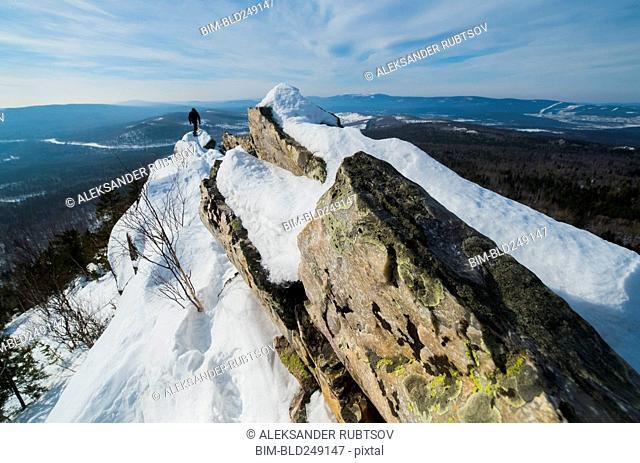 Caucasian man hiking on mountain in winter