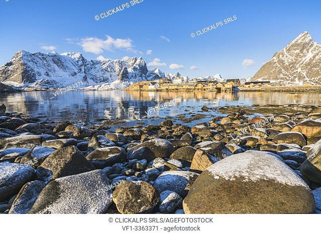 Sariskoy village in winter, with rocky beach in the foreground. Reine, Lofoten district, Nordland county, Northern Norway, Norway