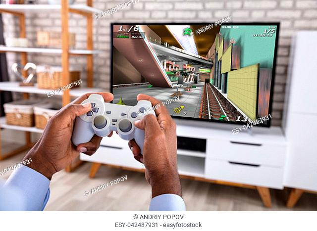 Close-up Of An African Man Playing Game With Joystick On Television