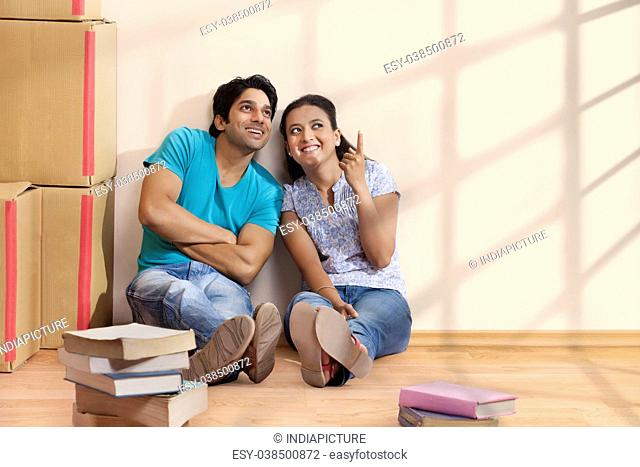 Happy couple pointing with finger to show something at new home